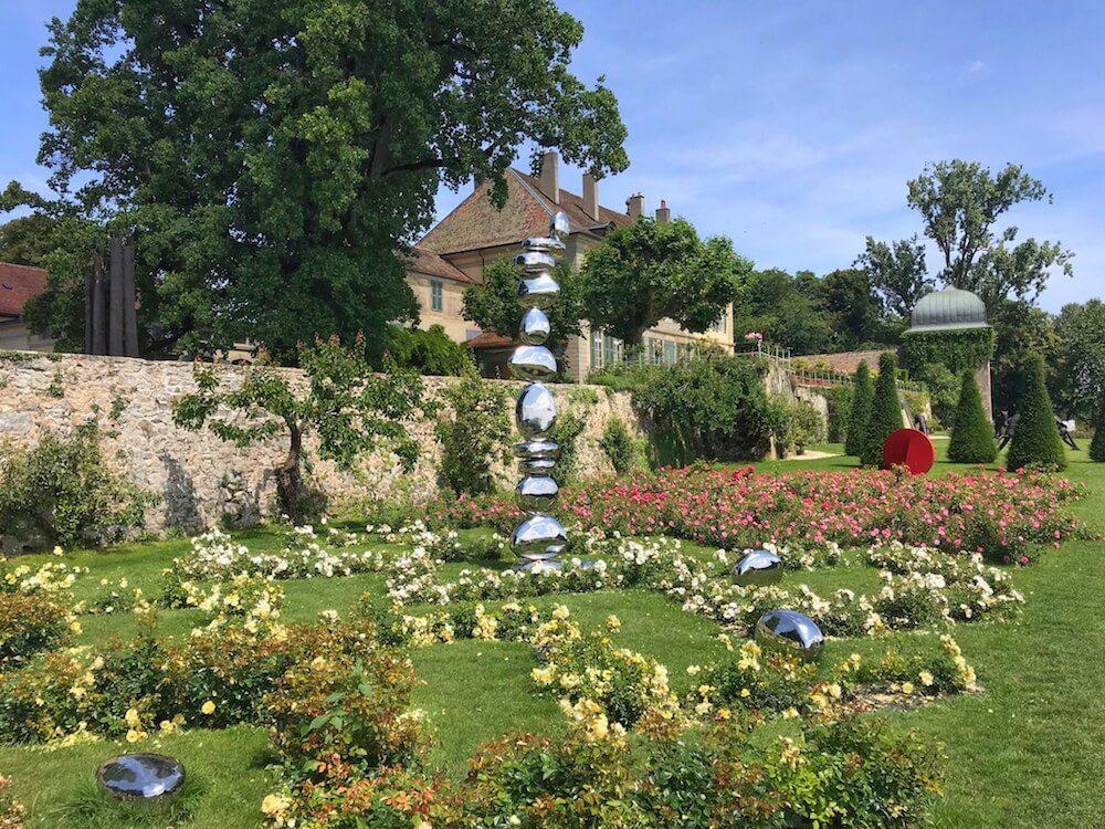 La sculpture de Pol Quadens entourée de roses en fleurs.